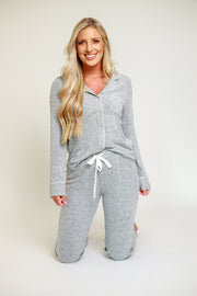 Woman kneeing in cozy pajama set in grey with button down top and pants with elastic waistband
