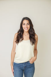 Woman wearing white cami top with scooped neckline and adjustable straps