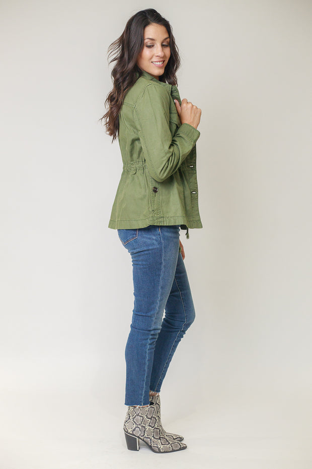 Woman wearing utility jacket in moss green with button details and a cinched waist