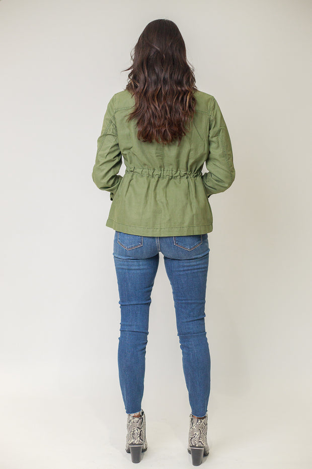 Back view of woman wearing moss green utility jacket from the back
