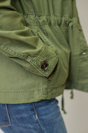 Close up of long sleeve moss green utility jacket featuring a button detailed on the sleeve