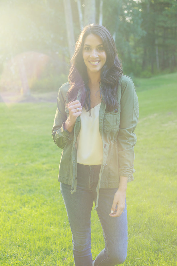 Woman wearing moss green utility jacket with button details and a cinched waist