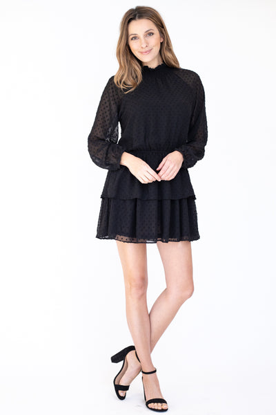Short black dress detailed with black dots and a high neck and a relaxed ruffled bottom