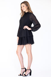 Side view of woman wearing black swiss dot long sleeve dress