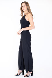 Side view of woman wearing flattering scalloped halter top neckline jumpsuit in black