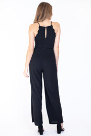 Back view of woman wearing flattering scalloped halter top neckline jumpsuit in black