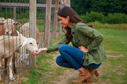 Woman outside feeding goats in moss green utility jacket with a cinched waist
