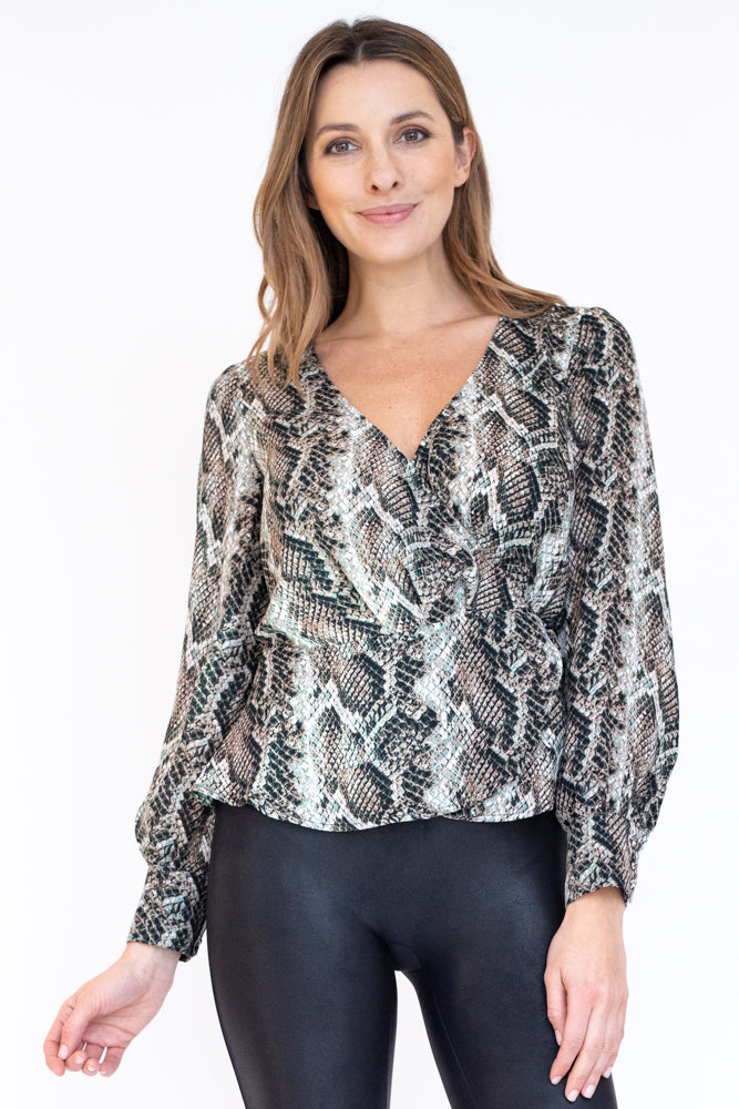 Woman wearing v neck wrap peplum top in snakeskin print