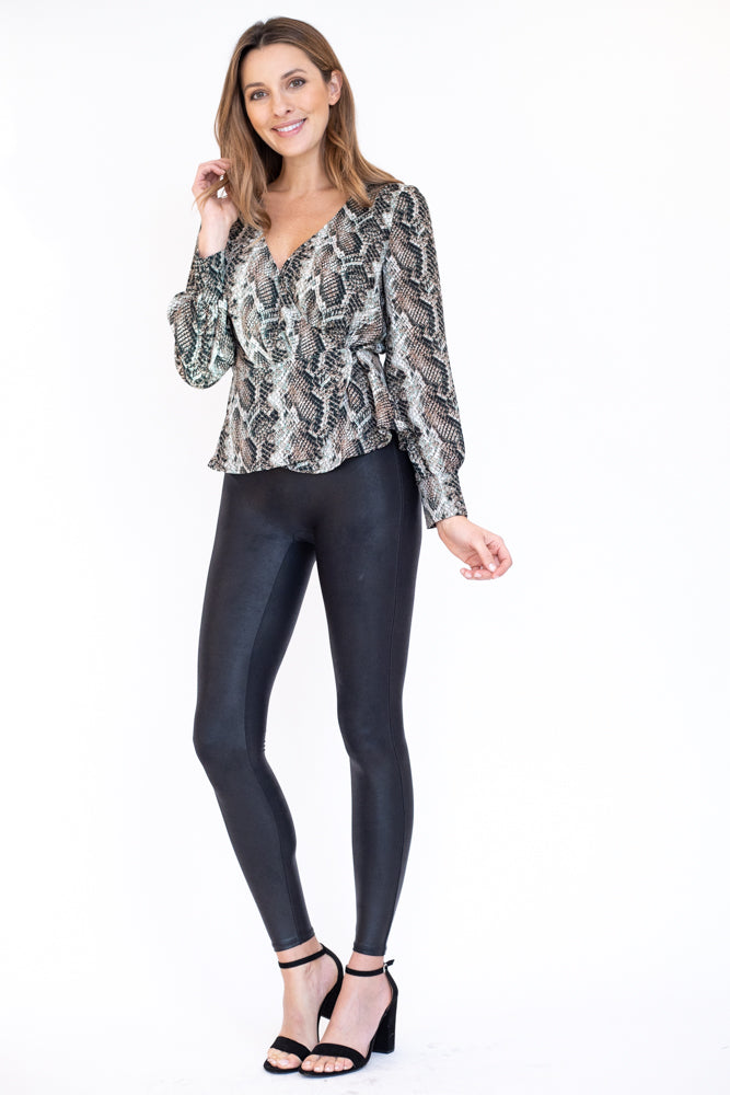 Woman wearing snakeskin peplum top with wrap closure and v neckline