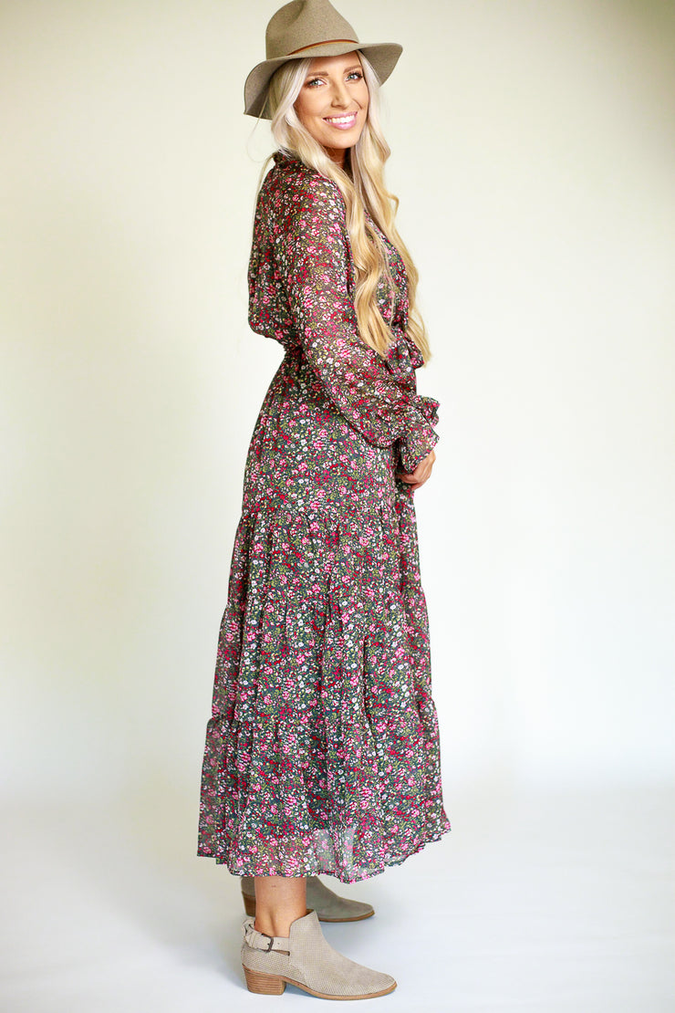 Side view of woman wearing a floral printed chiffon maxi dress with a cinched tie waist