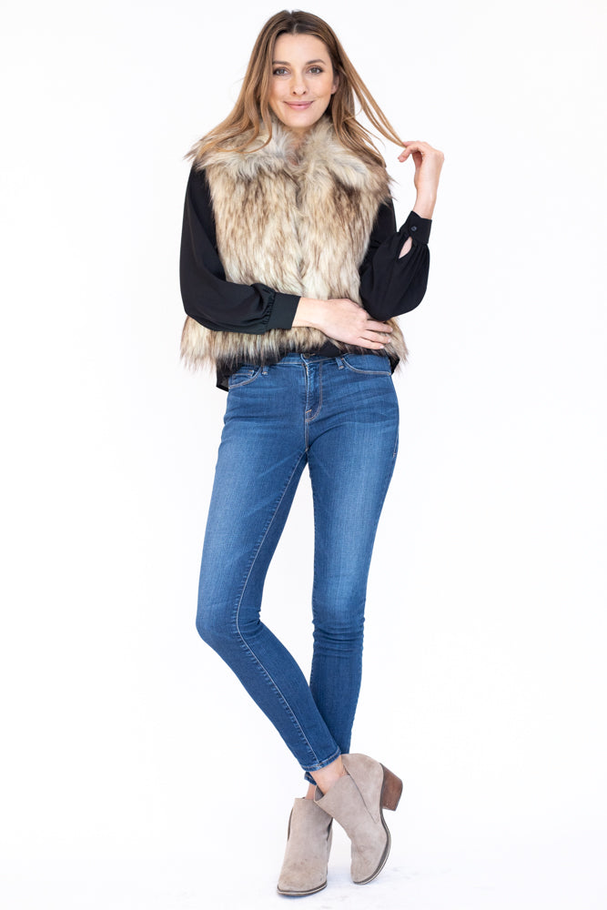 Woman wearing faux fur vest with shawl collar and cropped fit
