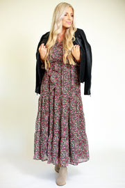 Woman wearing chiffon floral printed maxi dress with a leather jacket wrapped around her