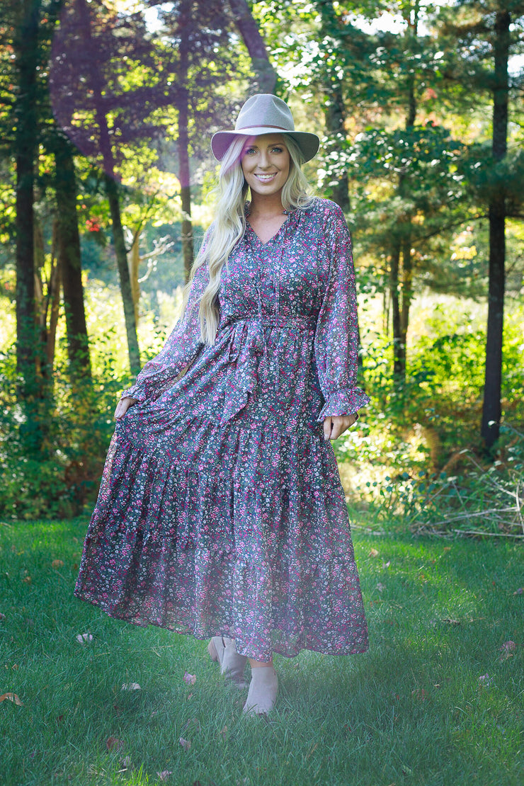 Woman standing outside in long sleeve chiffon floral printed maxi dress wearing a fall hat
