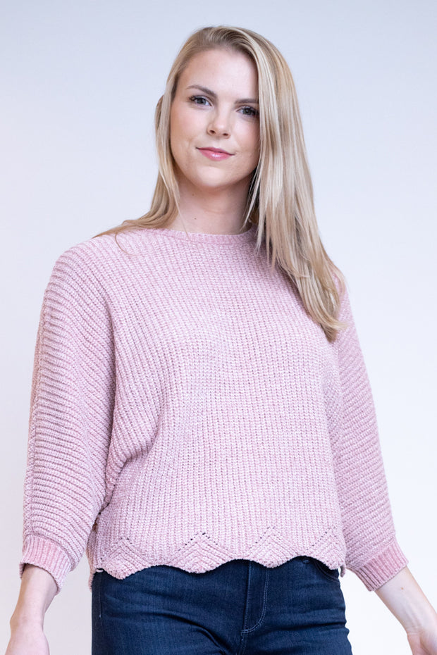 Woman wearing scalloped bottom sweater in pink rose color with gold specks
