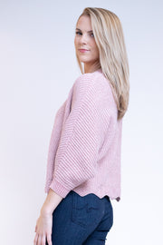 Side view of woman wearing scalloped edge sweater in pink rose color with gold specks