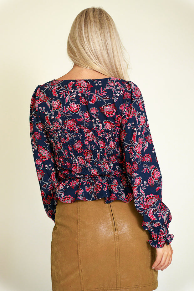 Back view of navy and magenta floral top with square neckline and slight peplum style