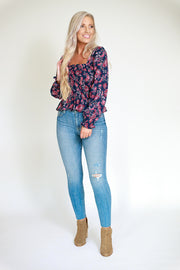 Woman wearing Navy and magenta floral top with square neckline and slight peplum style
