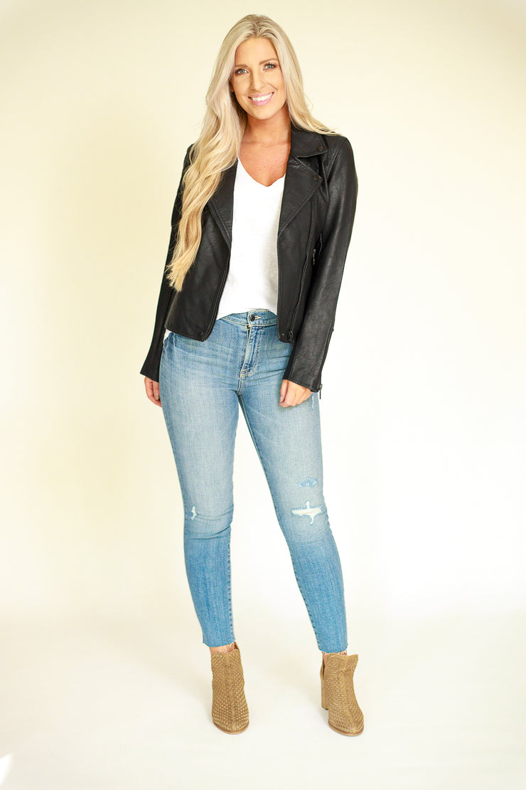 Far view of woman wearing classic vegan leather jacket in black