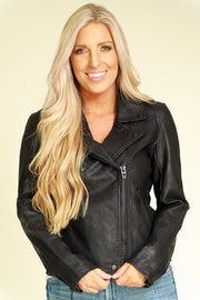 Woman wearing black vegan leather jacket fully zipped close