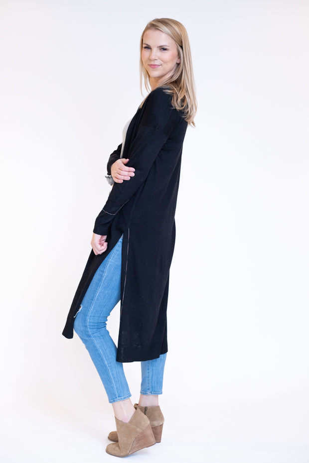 Woman wearing basic black duster cardigan with high slits