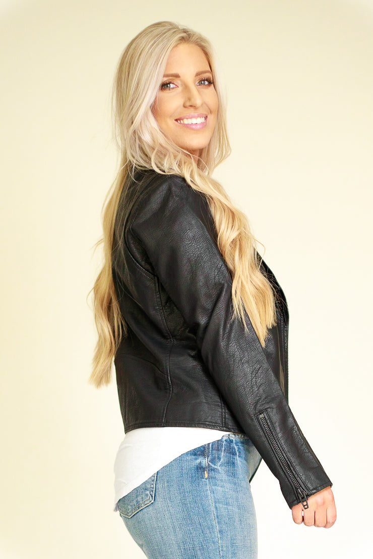 Side view of woman wearing vegan leather jacket in black