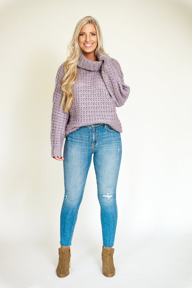 Far view of woman wearing chunky turtleneck sweater in a grey/lilac color