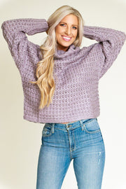 Woman wearing a grey/lilac chunky knit sweater with a wide turtleneck
