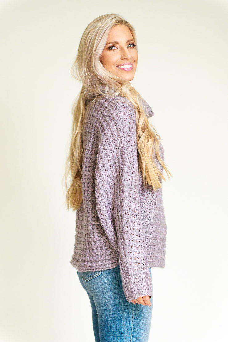Side view of woman wearing a wide chunky knit turtleneck sweater in lilac/grey color