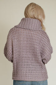 Back side of woman wearing wide turtleneck chunky knit sweater in grey/lilac color