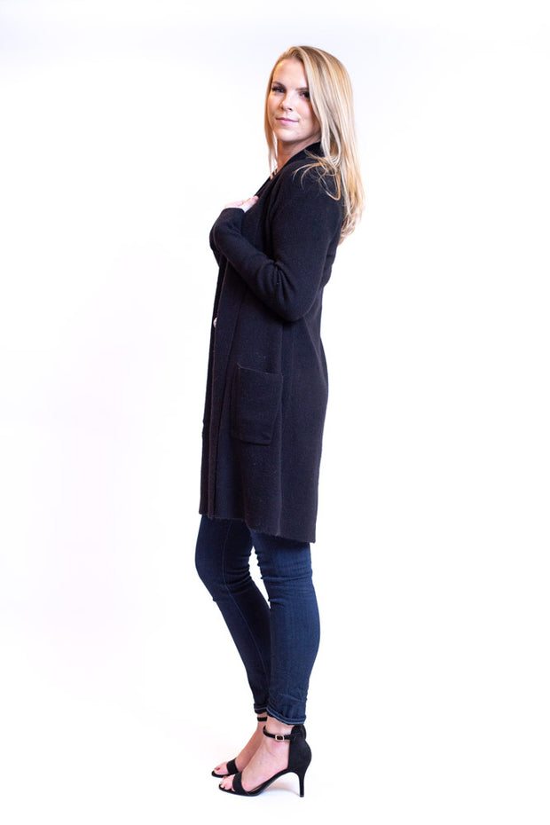 Side view of woman wearing long cardigan with slight shawl collar and pockets in a dark color