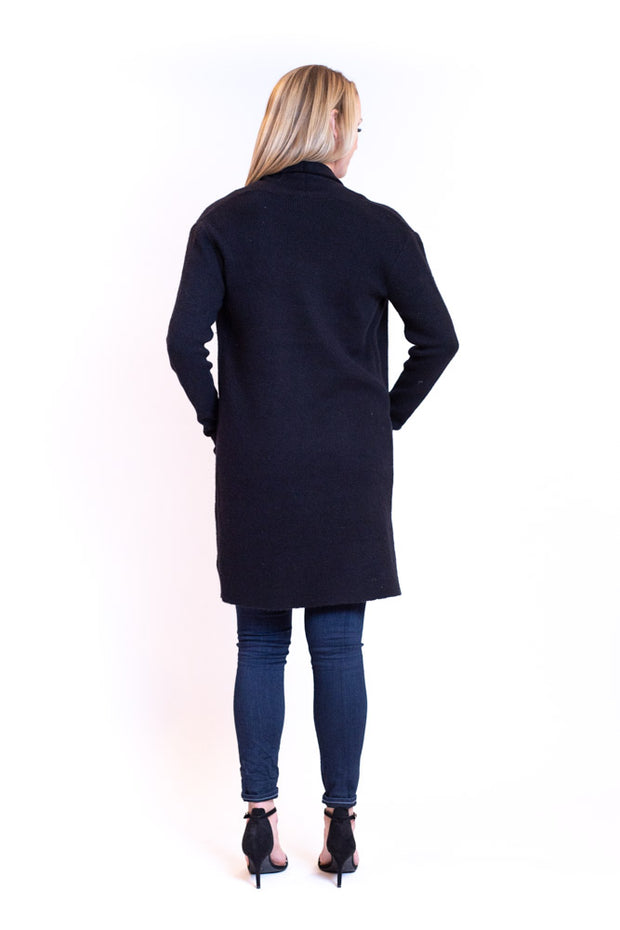 Back view of woman wearing longer length cardigan with pockets in a dark color