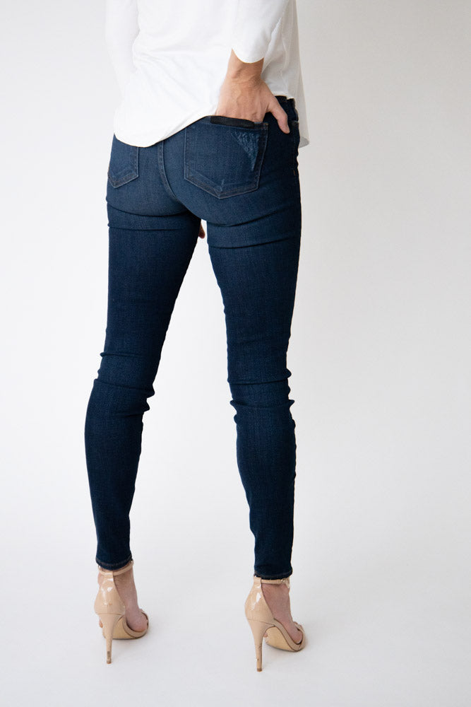 Back view of woman wearing dark wash high rise skinny jeans