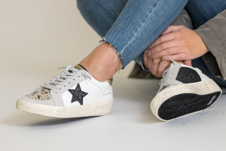 White classic sneakers with snakeskin detail and a black glitter star on sides