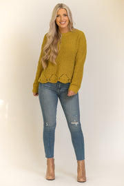 Woman wearing mustard yellow chenille sweater with scalloped edge at the bottom