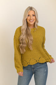 Woman wearing mustard yellow knit sweater with a scalloped bottom