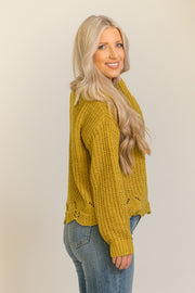 Side view of woman wearing chenille pullover in mustard yellow