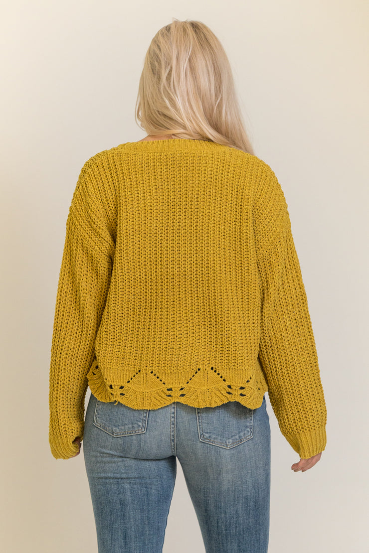 Back view of woman wearing mustard yellow chenille sweater with scalloped bottom