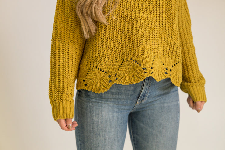 Close up of mustard yellow scalloped edge at bottom of sweater
