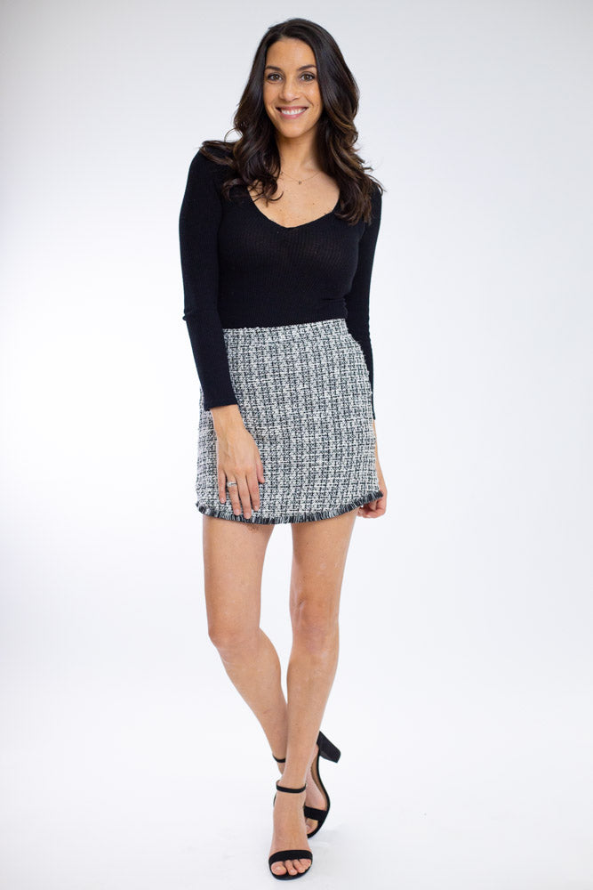Woman wearing black and white tweed tailored skirt