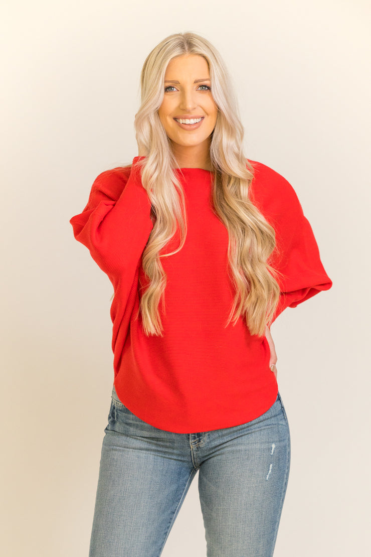 Woman wearing bright red dolman sleeve sweater