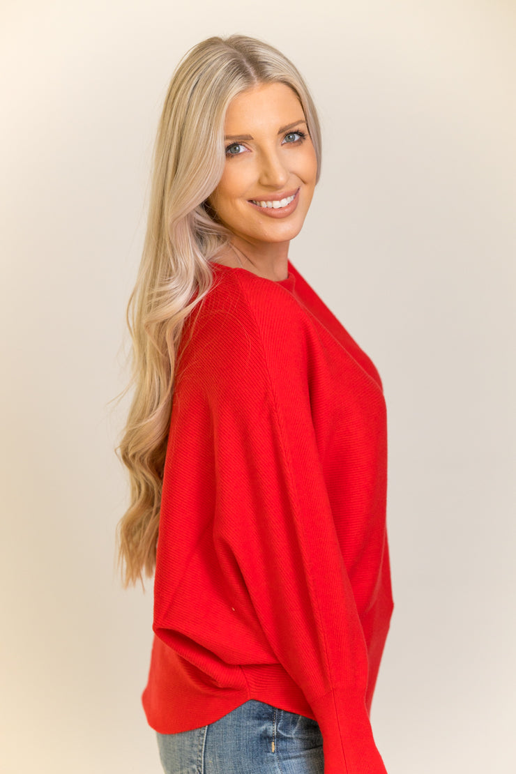 Side view of woman wearing dolman sleeve sweater in bright red