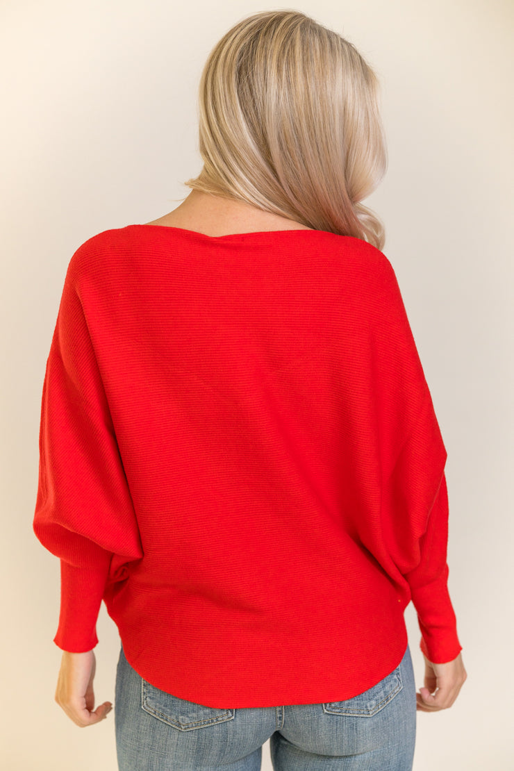 Back view of woman wearing bright red dolman sleeve sweater
