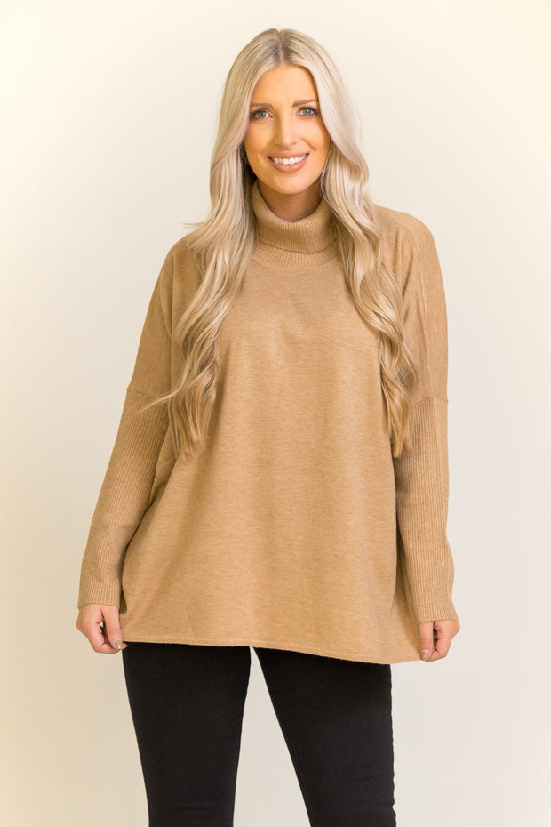 Woman wearing turtleneck sweater in camel color with an open slit in back