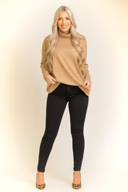 Woman wearing camel colored turtleneck sweater with black jeans and heels