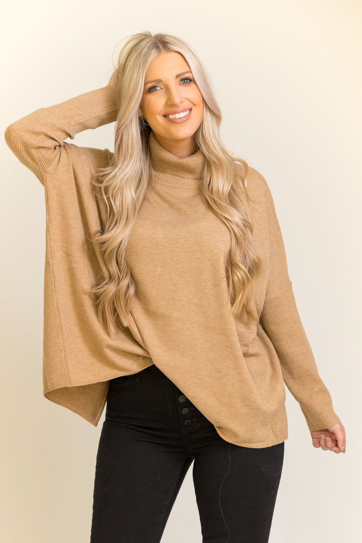 Woman wearing turtleneck sweater in camel color with open slit in the back