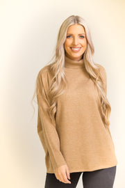 Close up of woman wearing camel colored turtleneck sweater