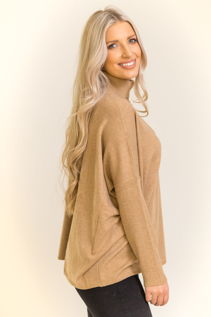 Side view of woman wearing turtleneck sweater with an open slit in the back in a camel color
