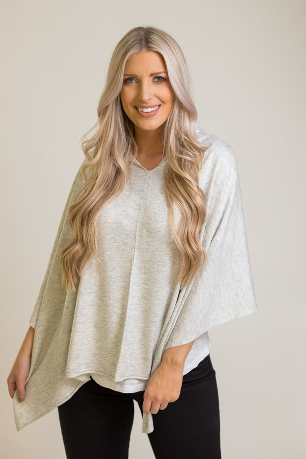 Woman wearing light grey poncho that can be styled 8 different ways