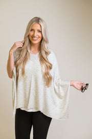 Woman wearing flowy light grey poncho that can be worn 8 different ways