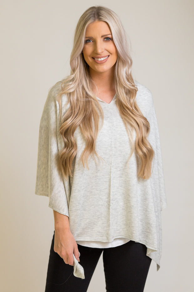 WOman wearing poncho in light grey color that can be worn 8 different ways